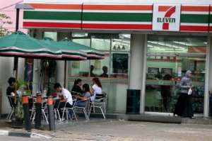 During daylight: People sit at tables in front of one of Jakarta's 7-Eleven convenience stores. JP/Nurhayati