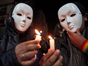 Seek the light: Activists wearing masks hold up candles during a demonstration marking International Day Against Homophobia in La Paz, Bolivia, on May 17. According to LGBT leaders, 24 people from the LGBT community have been murdered in the last 18 months in Honduras because of their sexual orientation. AP/Juan Karita
