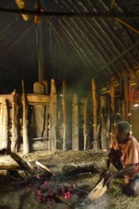 Keeping warm: An old Papuan lady tends to a fire inside a traditional Papuan house.