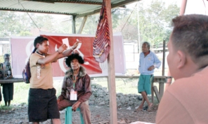 Look who I voted for: A woman in Woma district, Jayawijaya regency, holds her ballot up before placing it in a noken (traditional Papuan woven bag) in the January gubernatorial elections. (Antara/Rico)
