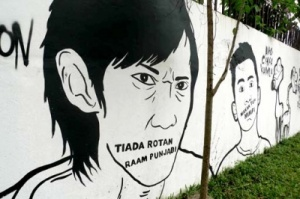 "Word play: The words ""Tiada rotan Raam Punjabi"" are painted under the nose of a picture of a man. Popo and Kampung Segart are playing with the Indonesian proverb ""Tiada rotan akar pun jadi"", to represent the overwhelming presence of sinetron tycoon Raam Punjabi."