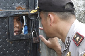 Iron: Pondok Gede sub-precinct head Comr. Dedy Tabrani speaks to an Ahmadi behind the locked gate of the Al Misbah Mosque in Bekasi on April 5. (Antara/Widodo S. Jusuf)